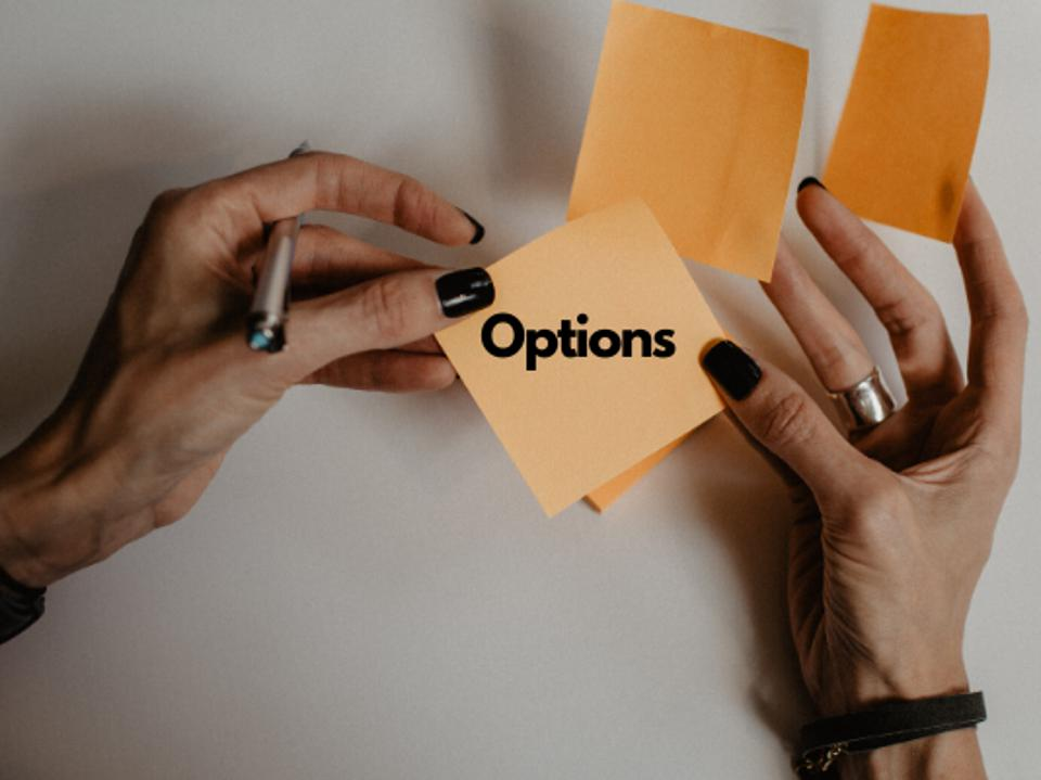 A pair of female hands sorts through some post it notes with the word options on one of them that she looks at.