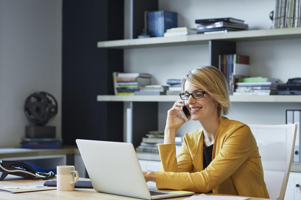 Businesswoman using laptop and smart phone at desk