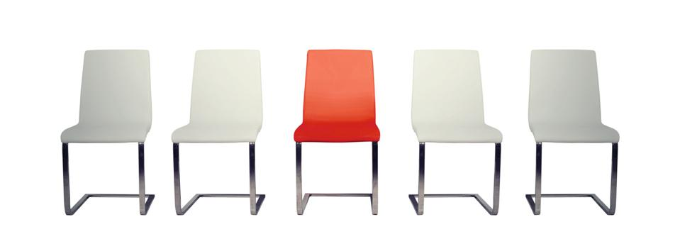 Row of five chairs. Four are white. The middle chair is red.