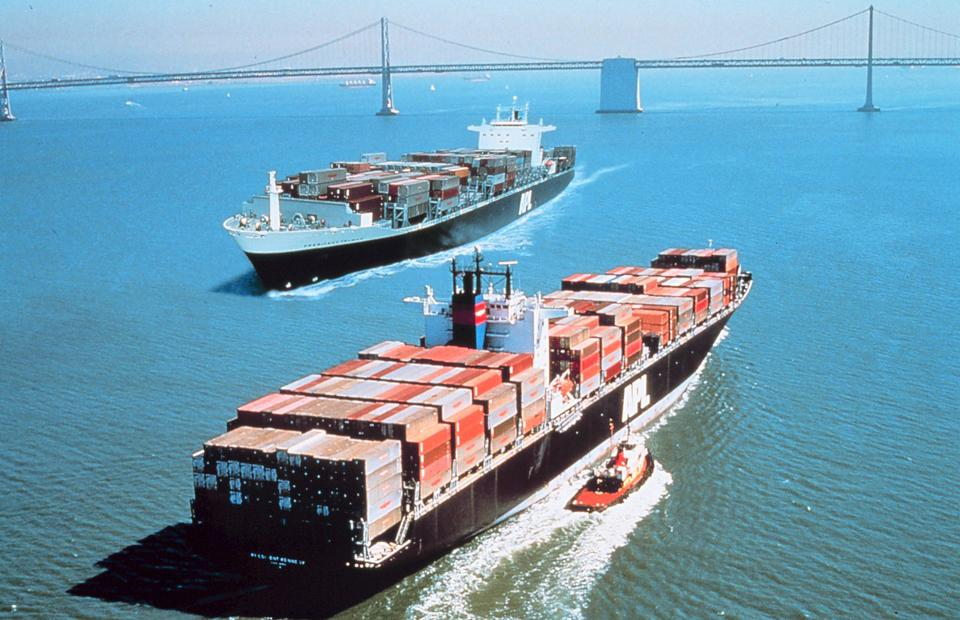 Two container ships pass, one accompanied by a tugboat, pass in San Francisco Bay.