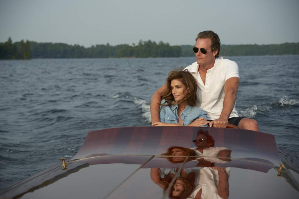 Rande Gerber and Cindy Crawford photographed on a classic varnished wood yacht