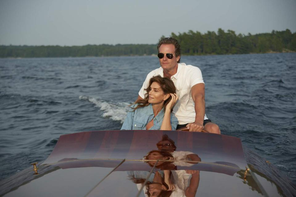 Rande Gerber and Cindy Crawford escape the crowds aboard a classic varnished wood powerboat.