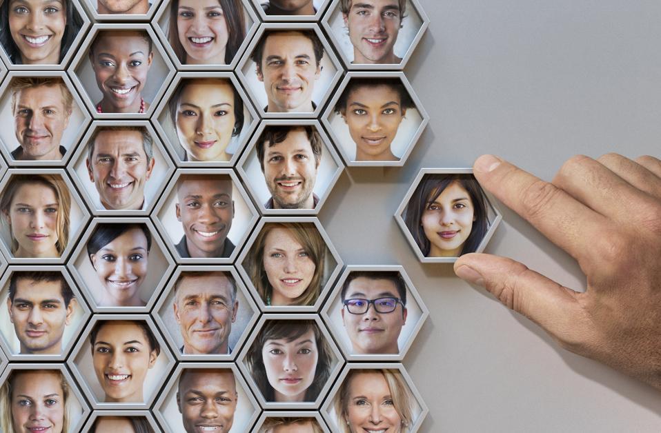 Group of hexagonal portrait pods, hand adding one. Team building concept.