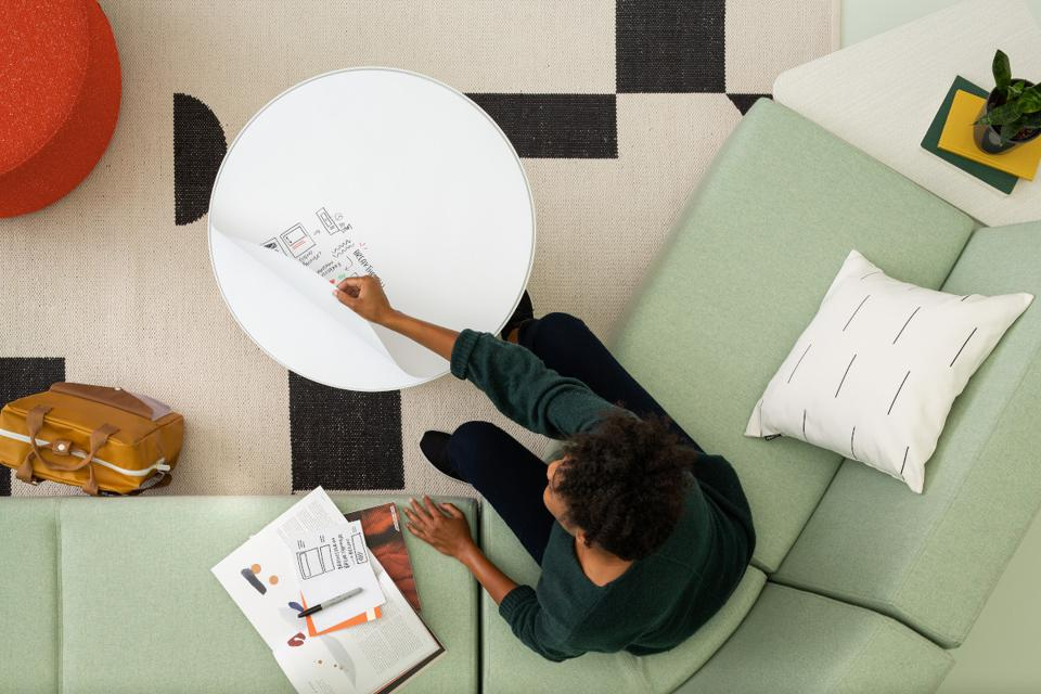 Overhead view of green couch with woman multitasking