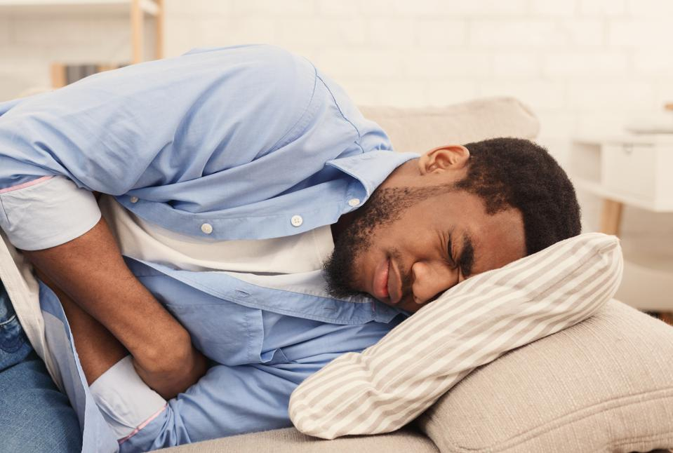 Black man suffering from stomach ache at home