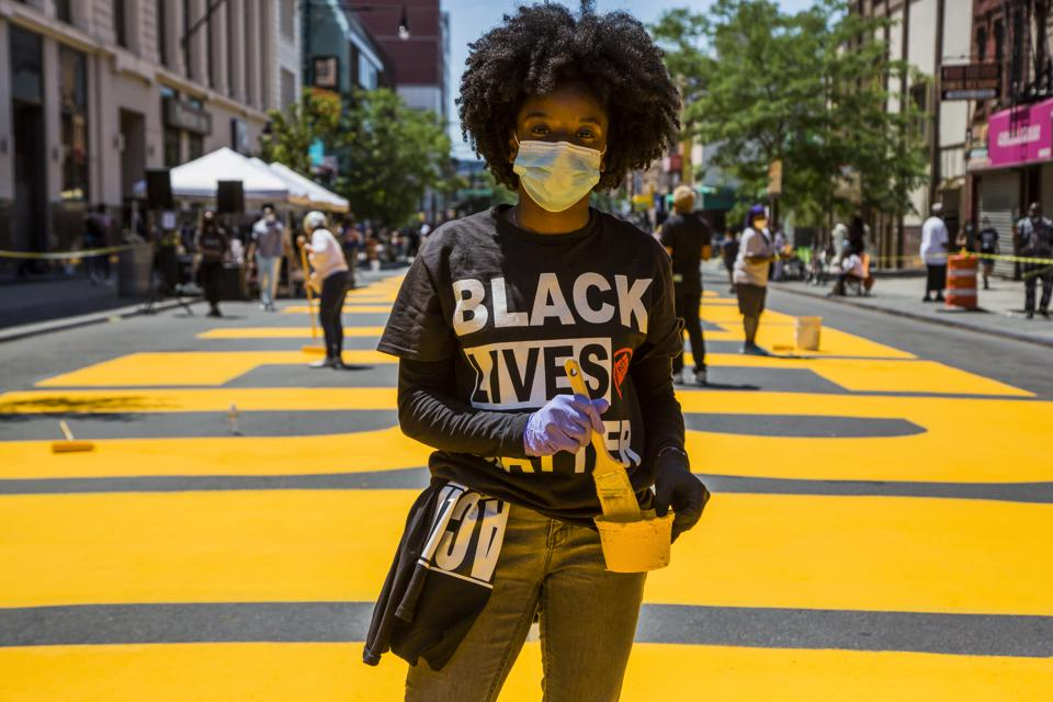 People paint a 'Black Lives Matter' Mural as protest against racism continue Nationwide