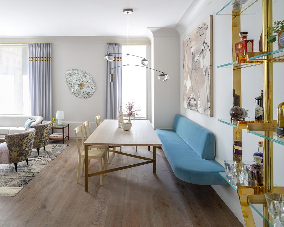 dining table with blue chair and gold shelving