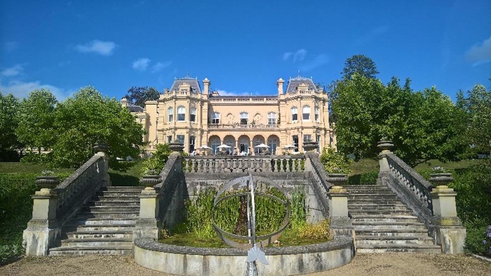 mansion house with stone steps leading to gardens