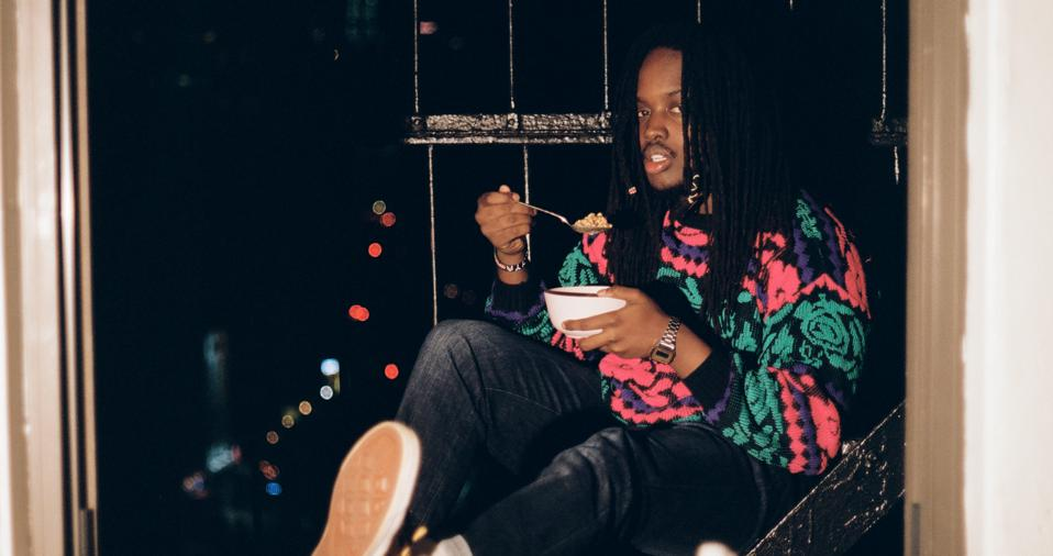 Musician maũ sitting on a fire escape with a bowl of cereal in hand.