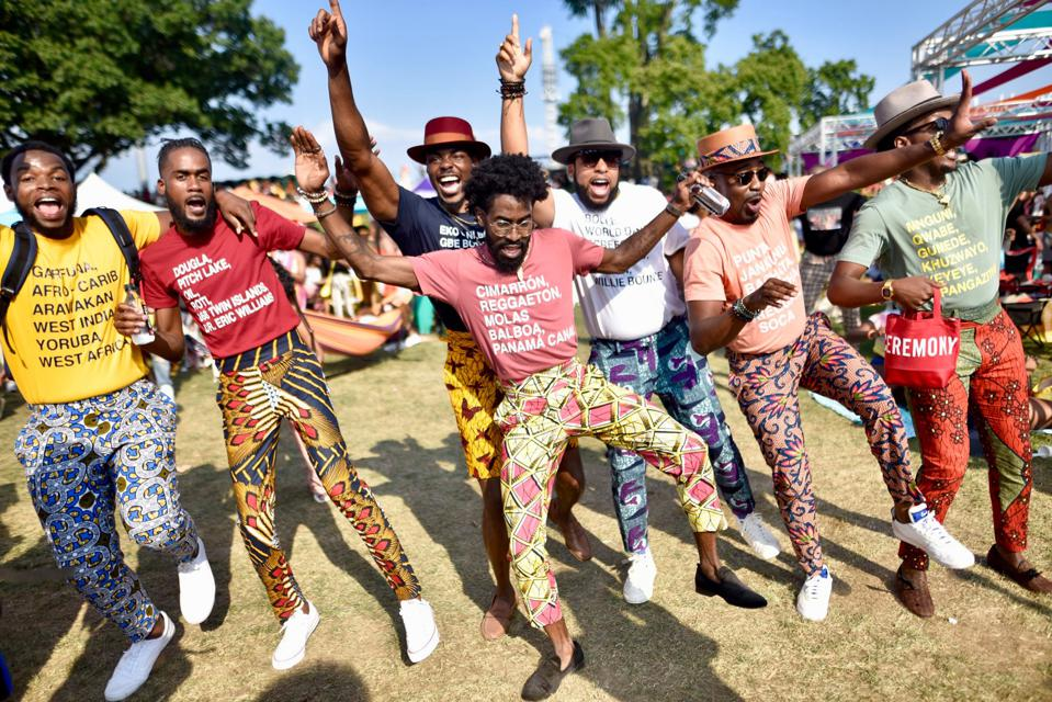 Seven men jump and wave their hands in the air at the Curlfest festival in 2019