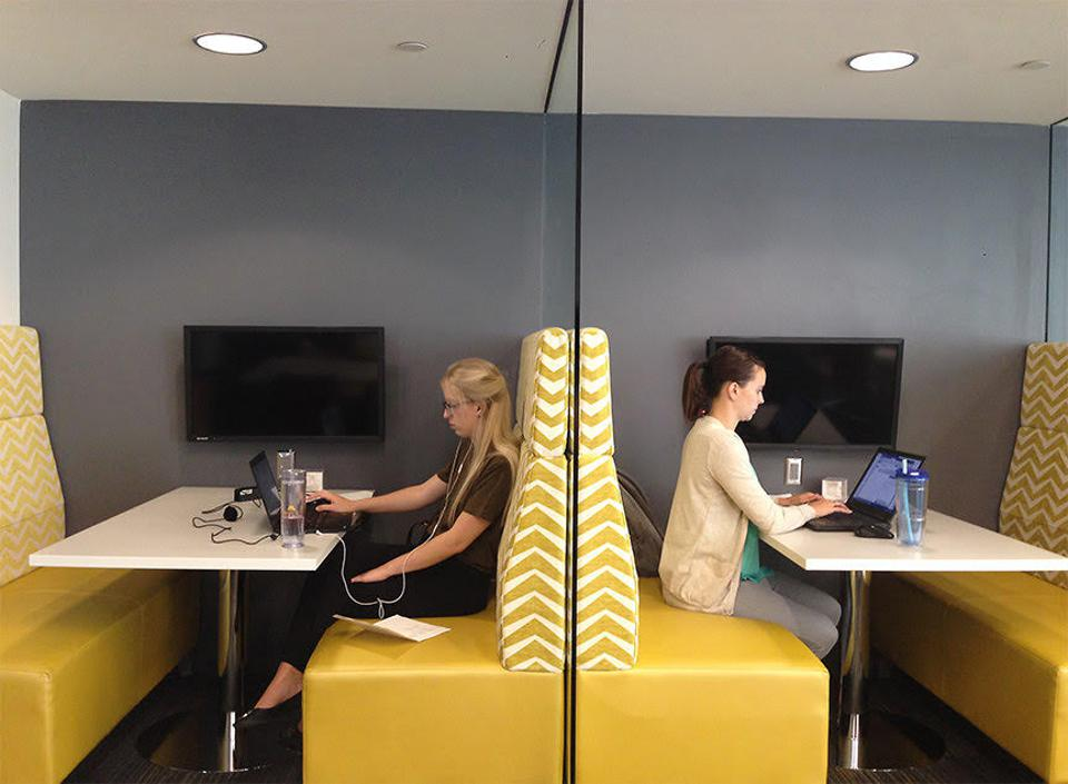 Office workers sit either side of a booth division