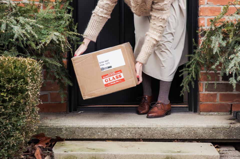 Woman picks a package up from her doorstep