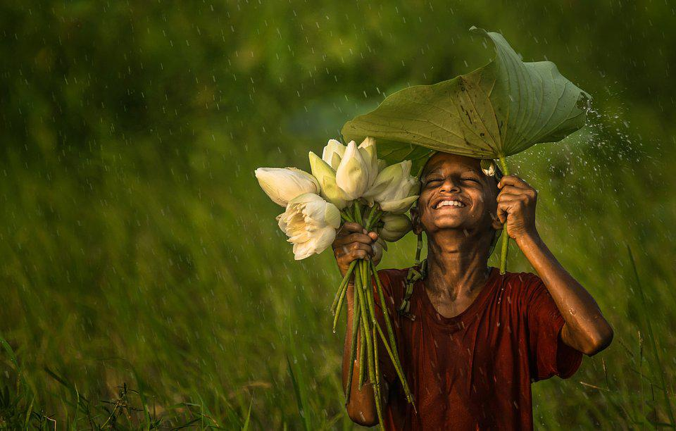 Bangladeshi boy with flowers under the rain.