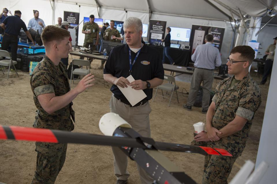 Two men in uniform stand in front of a cheap swarming drone built by the Navy.