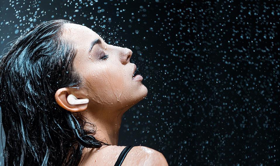 Woman wearing EarFun Air earphones is a shower of water