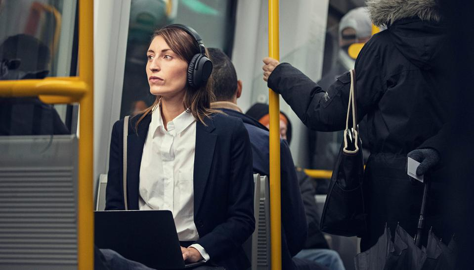 Woman on bus wearing wireless EPOS Adapt 660 headset