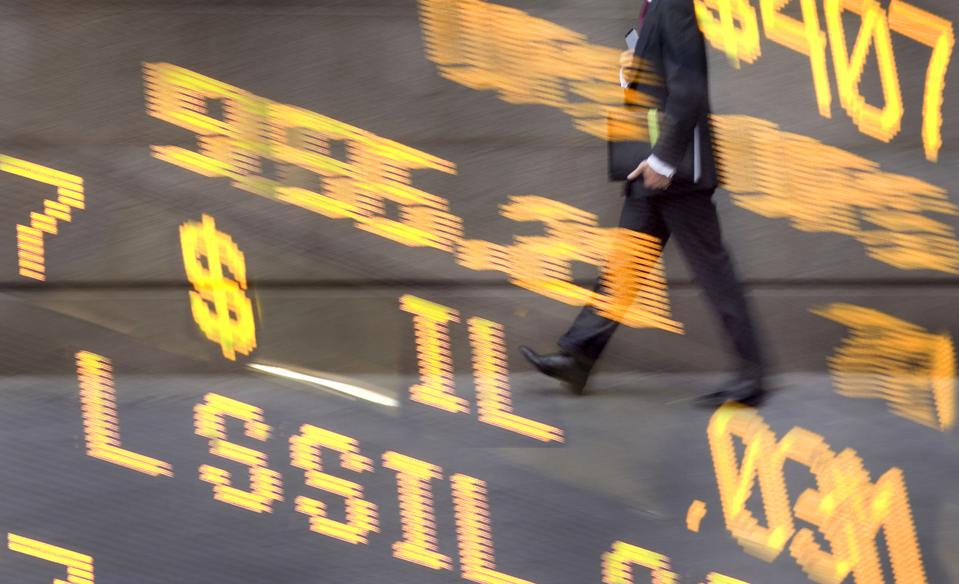 Composite image: businessman walking with stock readout board.