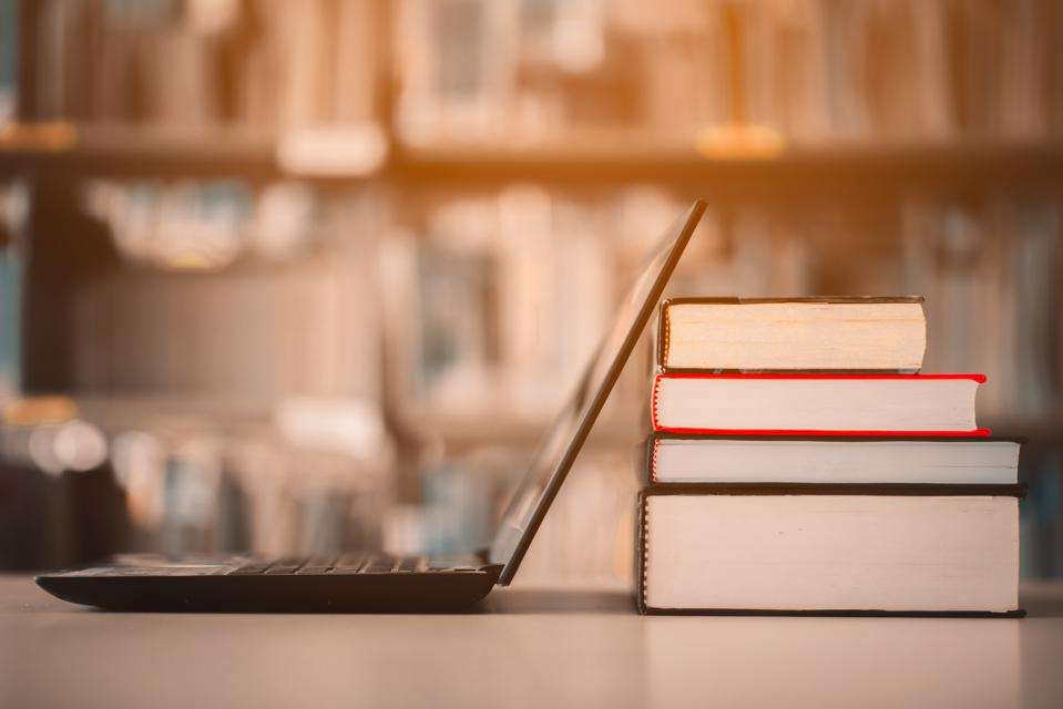 Bookshelves and laptops are placed on the library desk.E-learning class and e-book digital technology