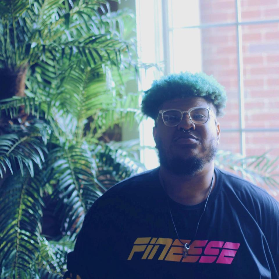 Indie soul singer Rob Milton standing in front of a large plant wearing a Finesse t-shirt.