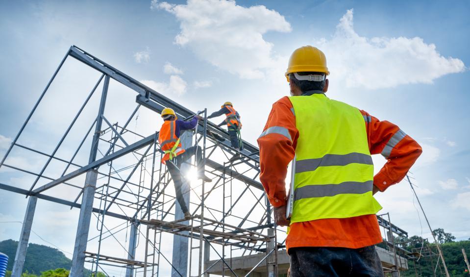 Engineer technician watching team of workers on high steel platform.