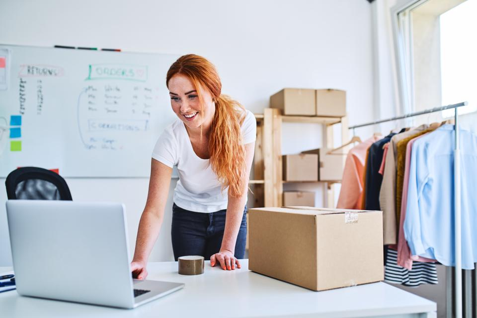 Young online business owner looking at laptop while preparing deliveries for clients