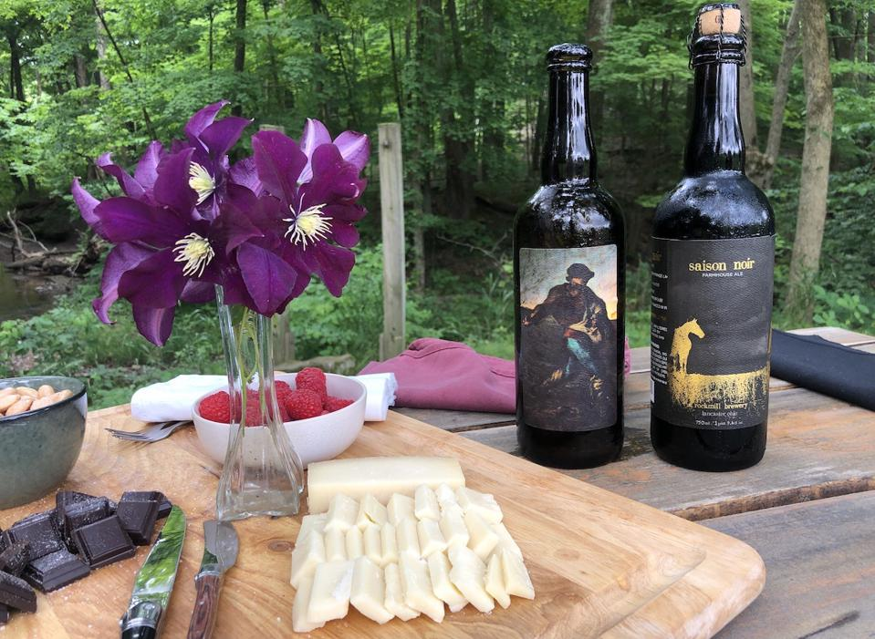 Two bottles of beer from Rockmill Brewing with a plate of cheese, chocolate and almonds by the river