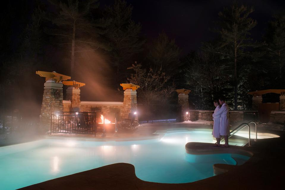 A couple stands in their bathrobes by the pool at Sundara in Wisconsin Dells