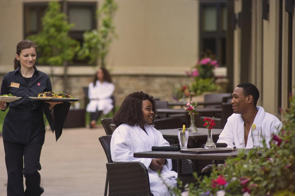 A Black couple dining in their bathrobes at Sundara Inn & Spa in Wisconsin Dells