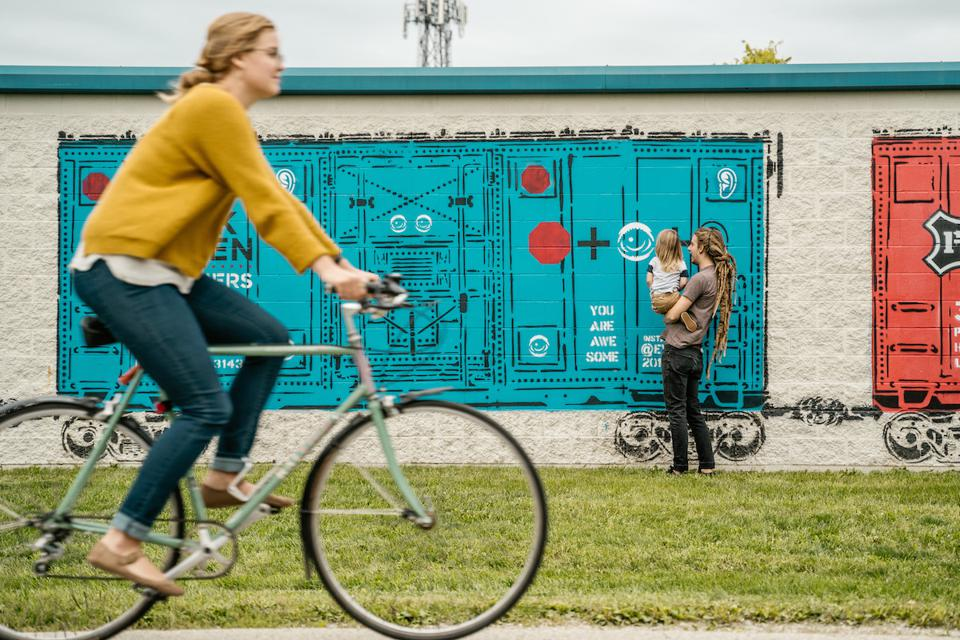A woman biking past a street mural on the Monon Trail in Indianapolis