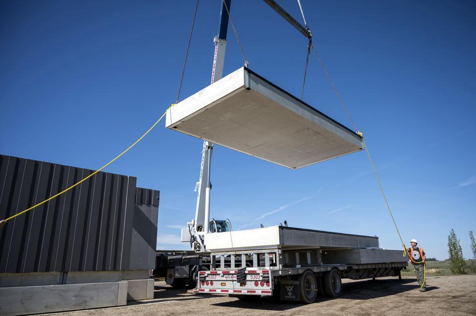 a crane lowers a slab onto a trailer for a Nexii project using Nexiite