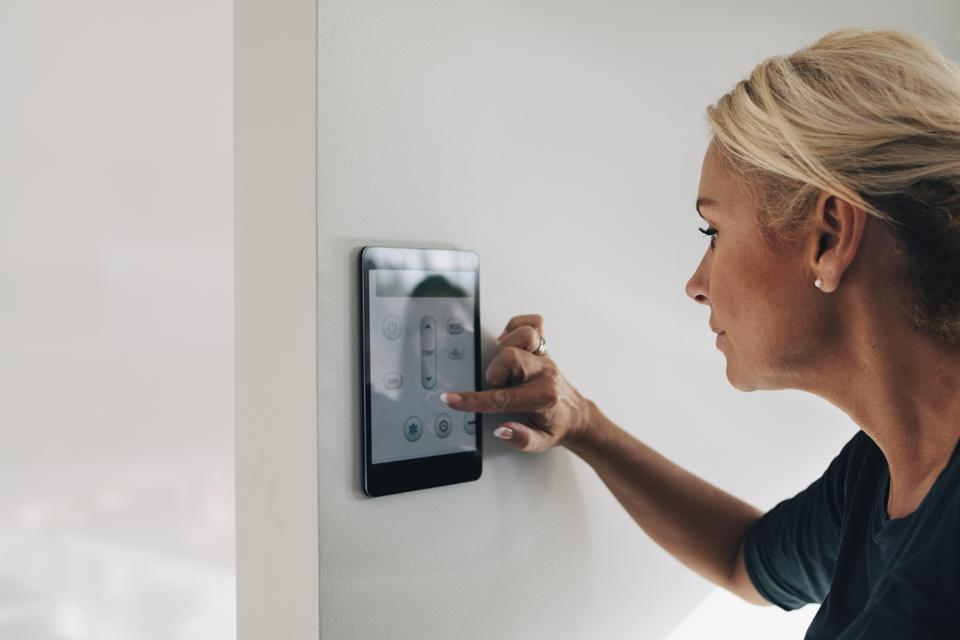 Blond woman adjusting thermostat using digital tablet mounted on white wall at home