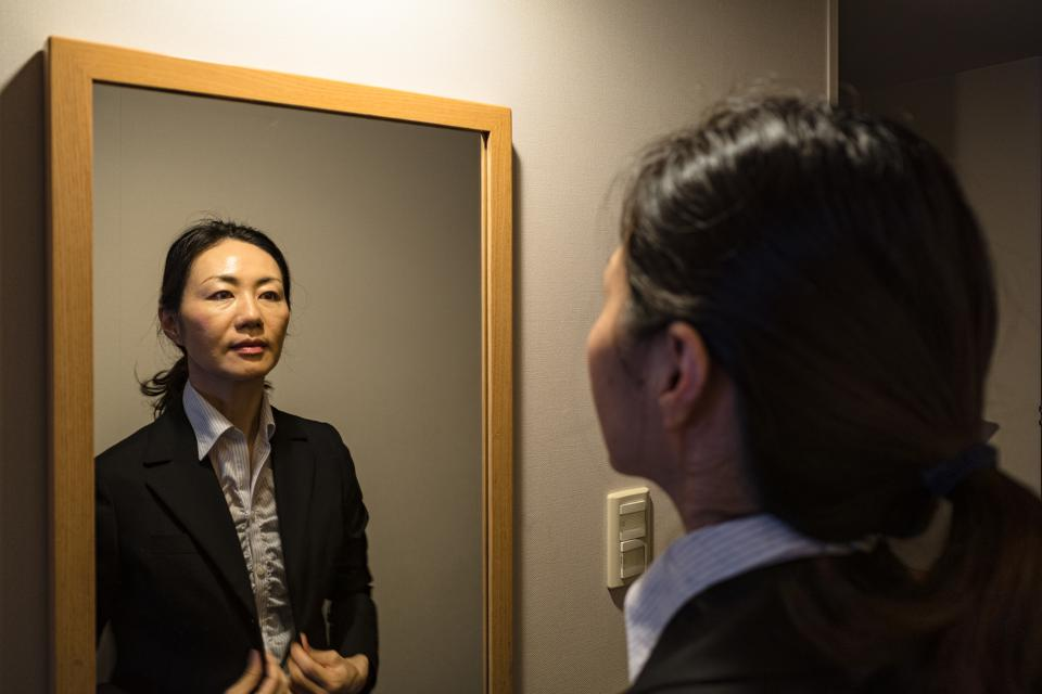 Female businessperson looking at the mirror in a dark room
