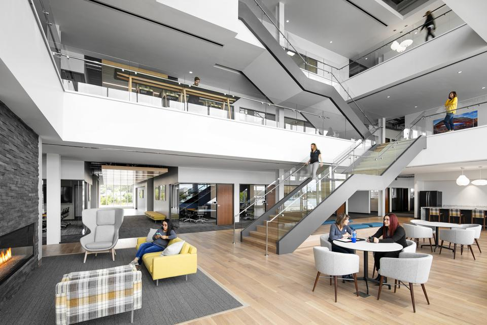 office lobby with staircase and lots of breakout spaces with tables and chairs