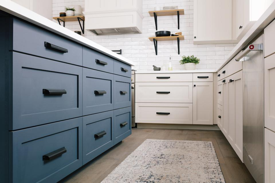 Black hardware on blue and white cabinets