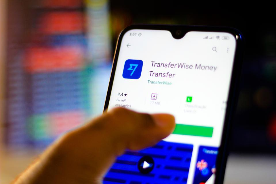 In this photo illustration the TransferWise app and logo is...
