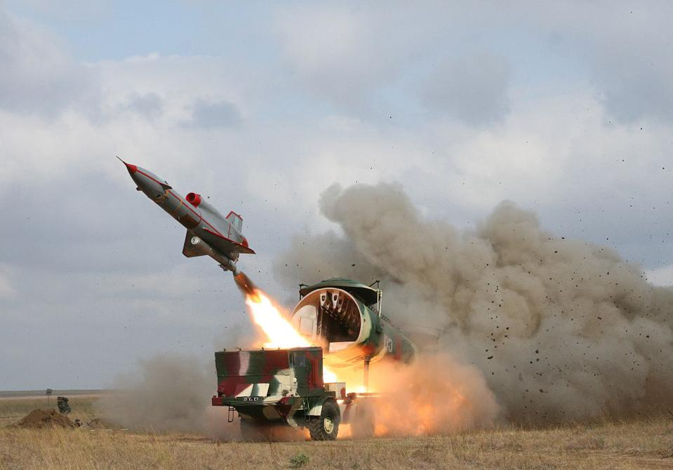 A missile-shaped drone blasts into the sky from a launch tube.