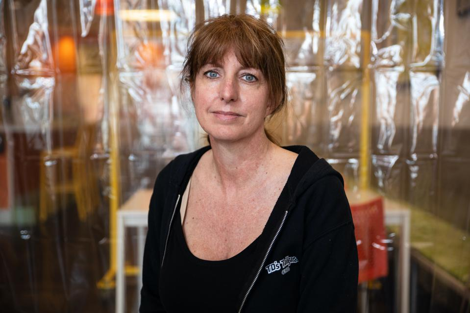 A woman poses in front of a plastic sheet.