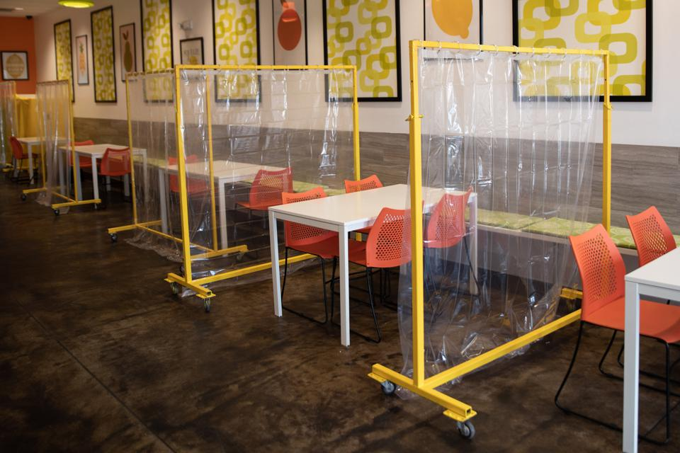 An empty restaurant has plastic curtains separating the tables.