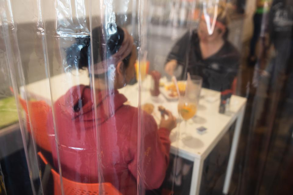 Customers at Twisted Citrus sit behind a plastic curtain.