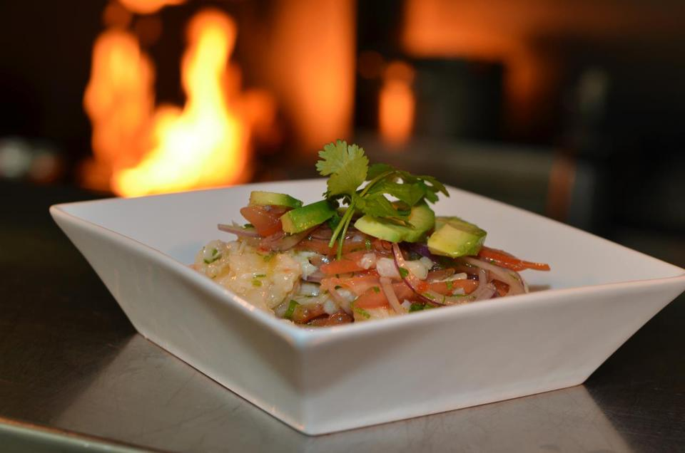 Cracked Conch conch ceviche made with tomatoes, red onions, avocado, lime juice, cucumber, water and cilantro.