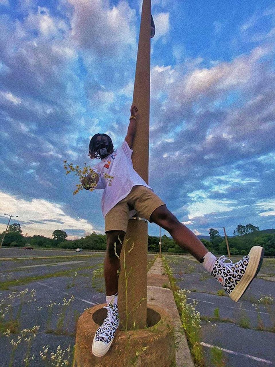 A young Black man playing on a pole.