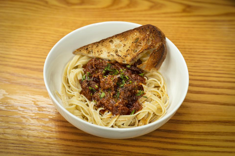 A bowl of Linguine With Braised Short Ribs in a Red Wine Sauce with fresh garlic bread.