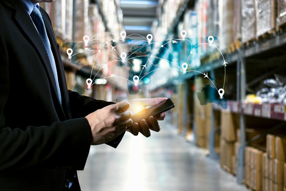 male manager hand holding tablet with AR application for check order pick time in smart factory warehouse, technology interface global partner connection for Logistic Import Export background
