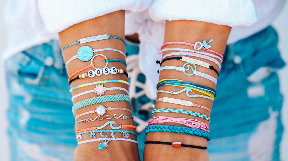 numerous colorful string bracelets adorn a woman's forearms