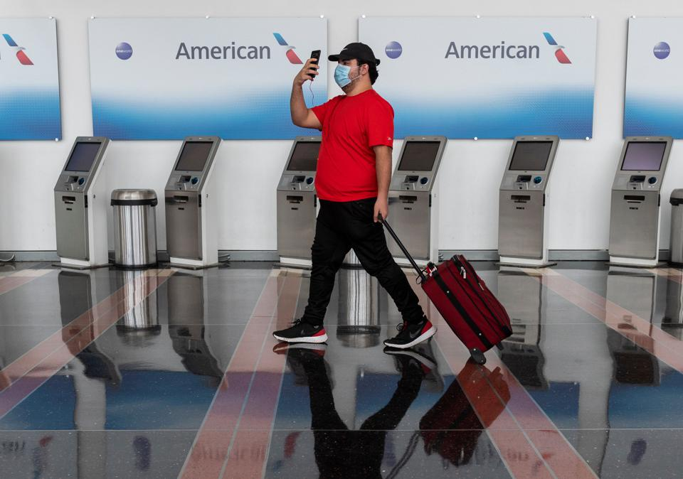 An American passenger walks past empty American Airlines check-in terminals in US