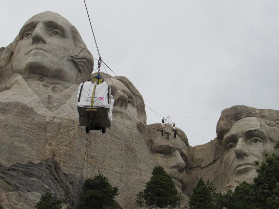 A large box attached to a cable makes it way up the stone sculptures of Mt. Rushmore.