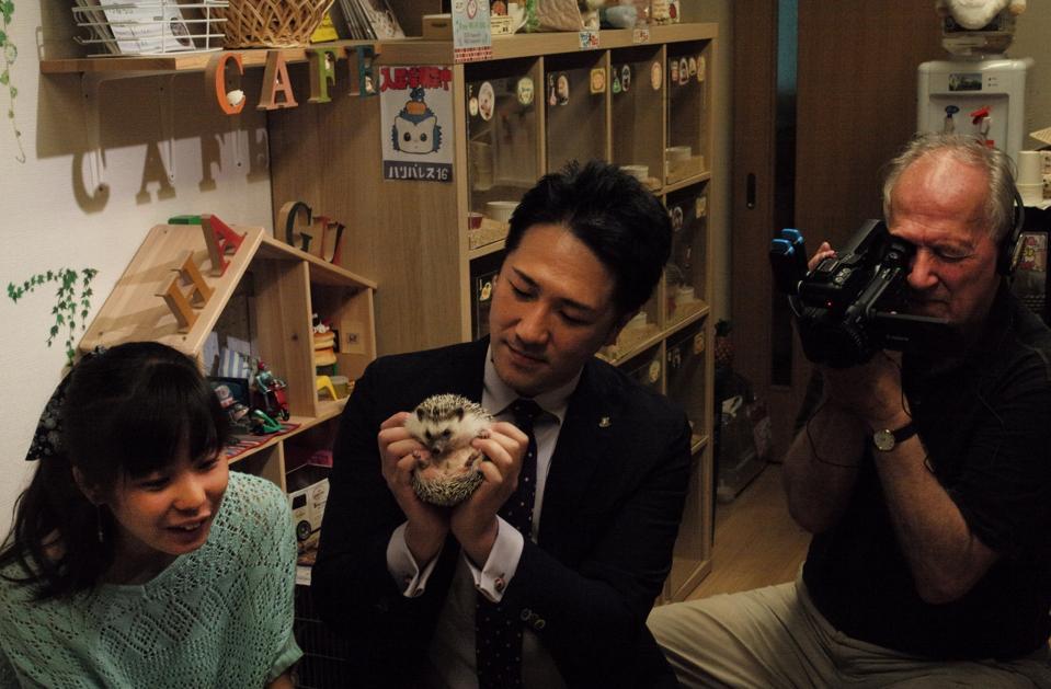 Werner Herzog filming Mahiro and Yuichi Ishii with a hedgehog in 'Family Romance, LLC'