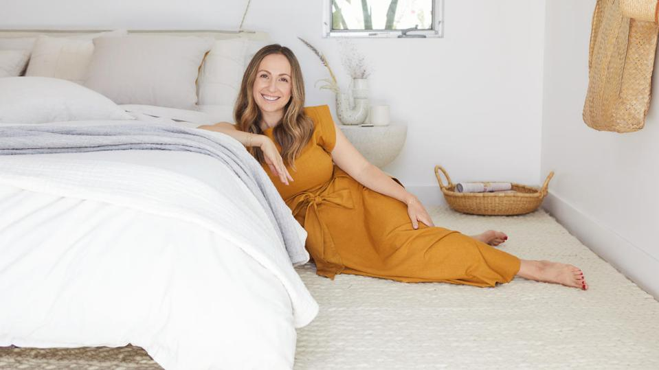 woman in orange dress laying next to bed