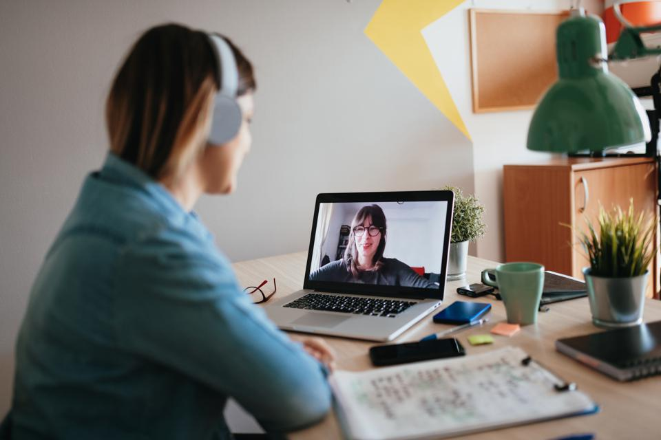 Young woman teleconferencing with sister on laptop on conference call