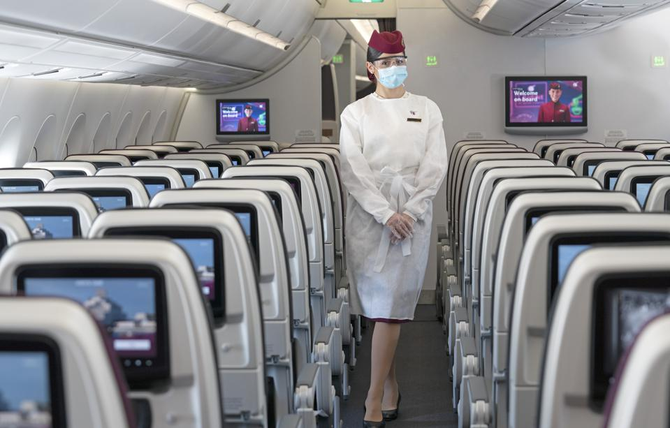A flight attendant in a Qatar Airways cabin in new protective equipment.
